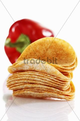 Oval paprika potato chips, stacking chips, stacked in front of a capsicum