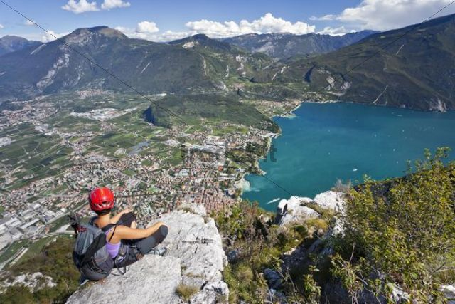 Climber on the Via dell Amicizia climbing route, overlooking Lake Garda and Riva, Trento, Italy, Europe