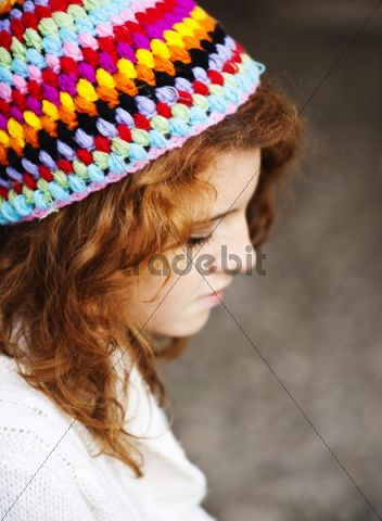 Girl wearing a colourful woollen cap with a dreamy expression, portrait