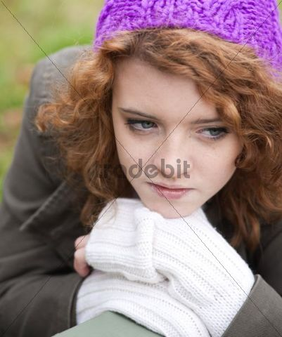 Girl wearing a woollen cap with a dreamy expression, portrait