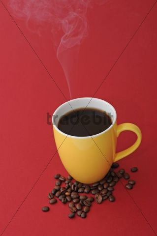 Steaming coffee cup with coffee beans