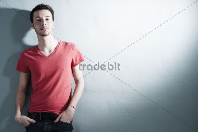Cool young man leaning against a wall