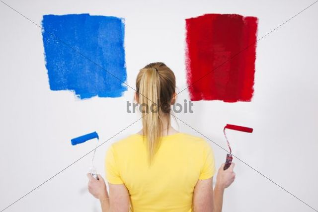 Young woman standing with two paint rollers in front of a wall with paint samples