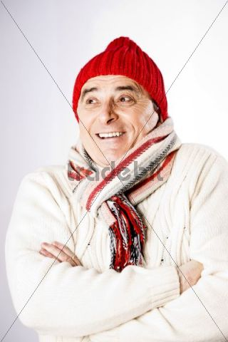 Friendly elderly man wearing a scarf and a woollen hat