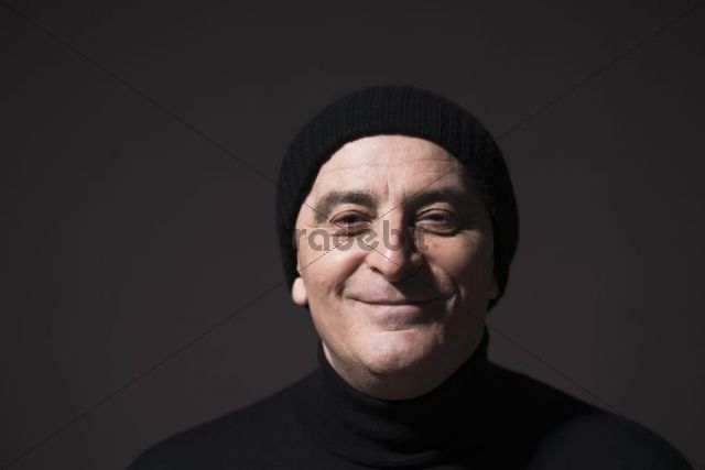 Smiling elderly man wearing a black woollen hat