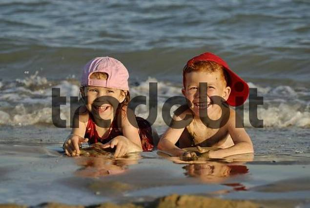 two children are lying in the water at the beach and are having fun