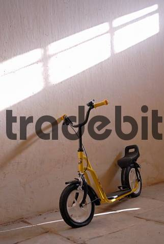 Scooter for children leaning against a wall