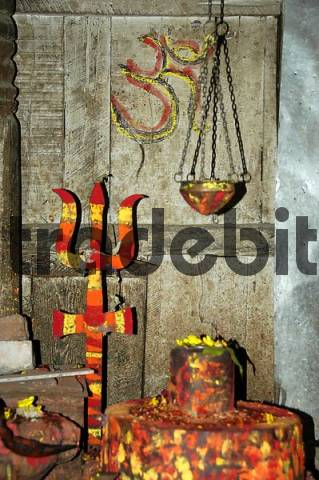 Shrine for god Shiva with a lingam and trisul red yellow and orange coloured Kathmandu Nepal