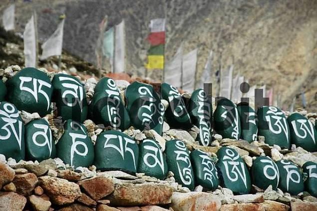 Tibetan script on green painted stones set in a row in front of prayer flags at monastery Tashi Gompa Phu Nar-Phu Annapurna Region Nepal
