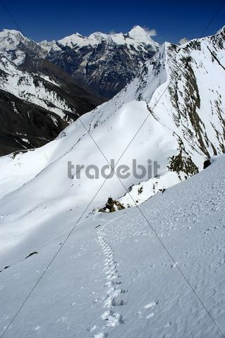 Footprints in the snow above Kang La pass with mountain Kang Guru in the background Nar-Phu Annapurna Region Nepal