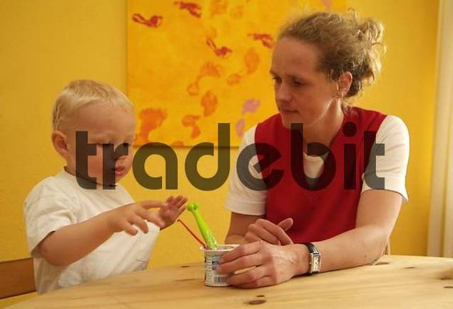 mother feeds child with yogurt