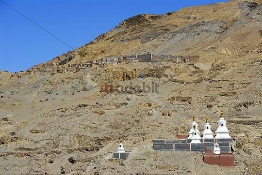 Tibetan Buddhism decayed building above white stupas with grey and dark red painted walls Sakya Monastery Tibet China