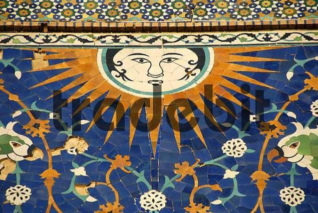 Face of the sun with rays as artful decorative maiolica on the portal of Nadir Divan-Begi Madrasah Bukhara Uzbekistan
