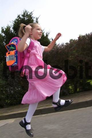 6 year old girl in pink dress running happily home after first school day, Schleswig-Holstein, Germany