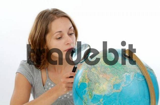 woman with loupe looking at globe