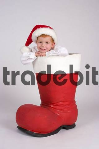 child in a huge Santa Claus boots for christmas