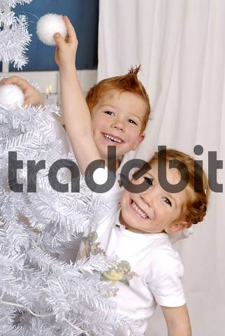 two children are decorating a christmas tree