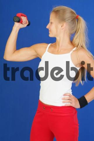 young woman trains with dumbbells