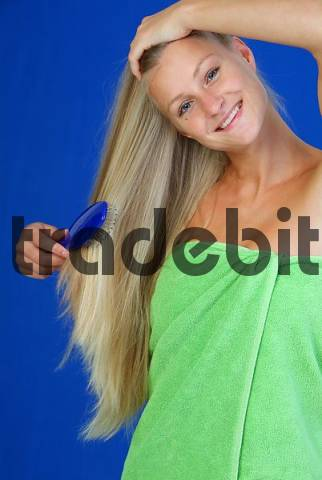 young, blond woman brushes her hair