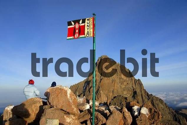 Kenyan national flag at Point Lenana 4985 m with rocky mountain summit Batian 5199 m in the background Mount Kenya National Park Kenya
