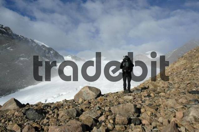 Mountaineer standing on boulders in front of a glacier Kharkhiraa Mongolian Altai near Ulaangom Uvs Aymag Mongolia