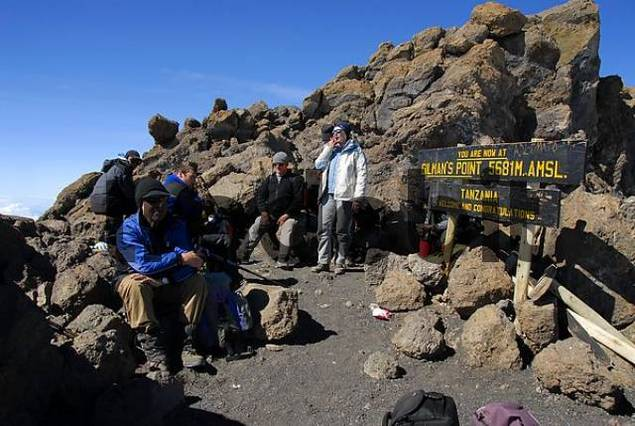 Successful group of mountaineers at the sign on the summit Gilmans Point 5681 m crater rim Kilimanjaro Tanzania
