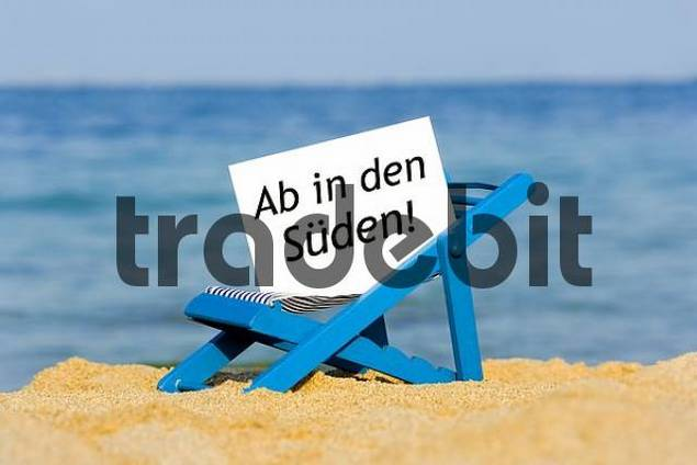 a deckchair with a sign on the beach