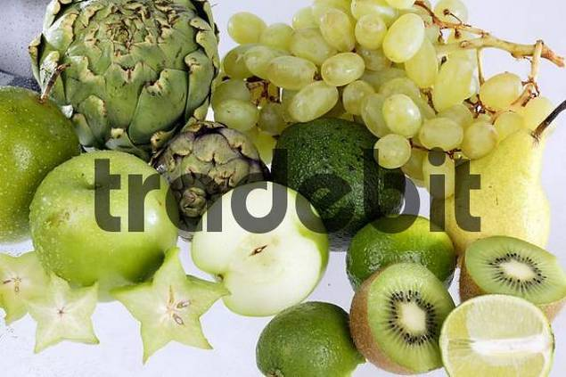 different green fruit like apple, Kiwi, grapes, partly cut open, on white background