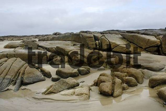 Granite rocks in tidal zone of sandy beach at the Altanic coast of Donegal on a foggy day, Ireland