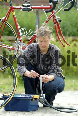 woman repairs bicycle