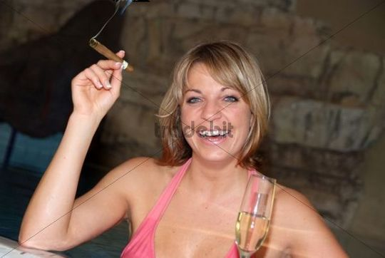 young woman with sparkling wine and cigar in pool