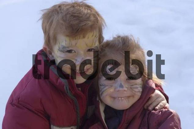 two children with painted faces as cats for carneval
