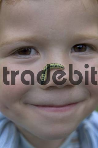 child with a caterpillar in the face exploring the nature nature games