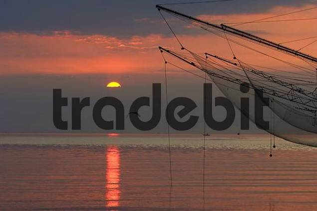 fishing nets on the coast at sunrise, red coloured sky and sea