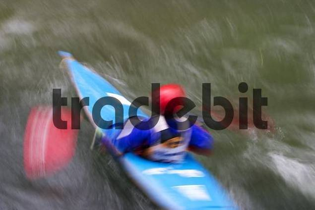 Blured picture of an fast kajakdriver with red helmet an blue boat  Isar , munich.