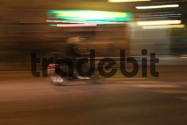 Blured picture of a person with white helmet driving a scooter in the night of barcelona Spain.