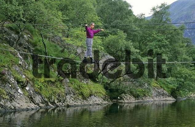 hiker crossing river on rope bridge in Glen Nevis near Fort William Scotland