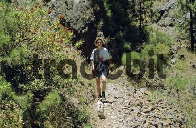 PR Woman with little dog hiking at Caldera de Taburiente, La Palma, Canary Islands, Spain