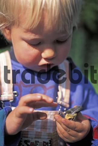 Two-year-old holding a snail MR