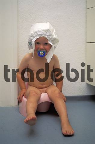 Two year old boy sitting on the pot with a napkin on his head MR