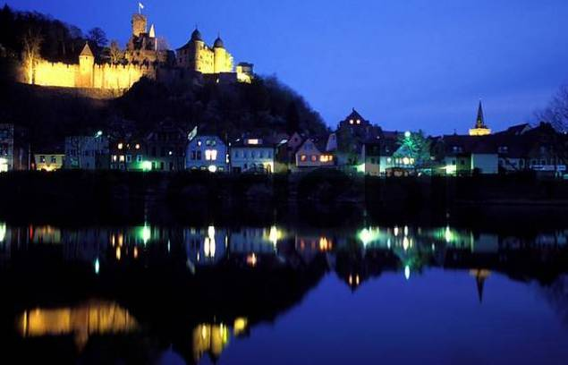 Germany: Wertheim on the Main river, Bavaria, reflection of the castle and city lights on the Main-river