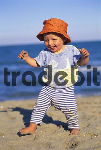 One year old boy learning to walk at the beach