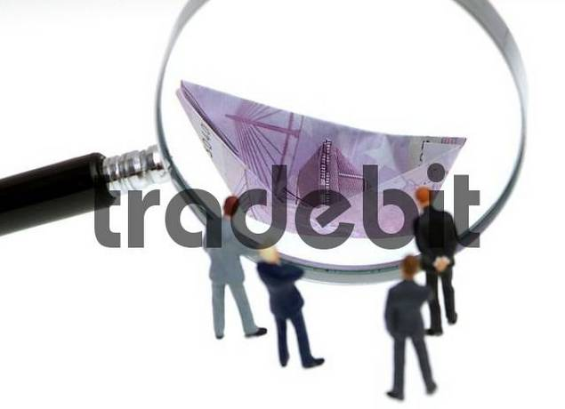 businesspeople looking through a loupe on a papership made of euro banknote