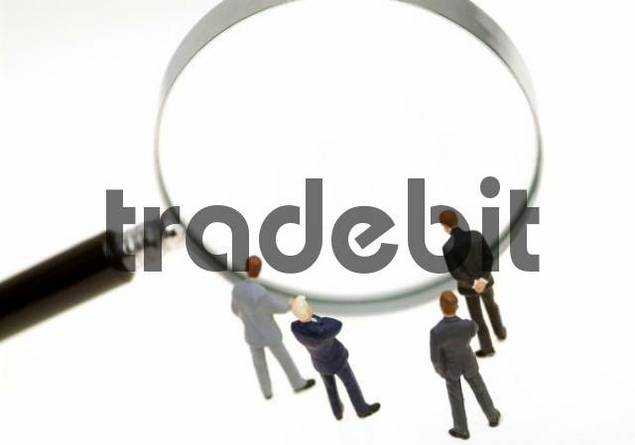 business people looking through a loupe