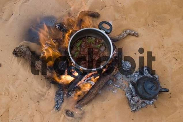 dinner and tea cooking on a fire place in the sand, Libya