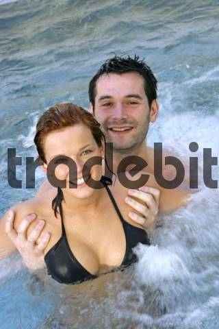 Laughing young couple in a swimming pool