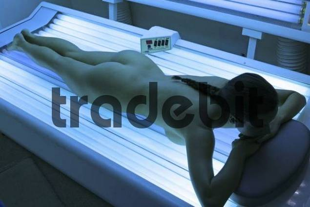 Young woman laying on a tanning bed