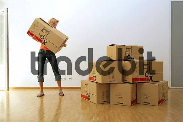 Young blonde woman carrying cardboard boxes, moving