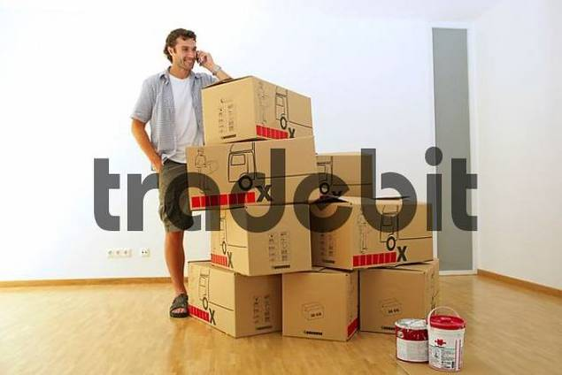 Young man making a phone call behind a pile of cardboard boxes, moving