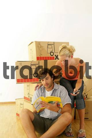 Young couple browsing through the Yellow Pages in front of cardboard boxes, moving